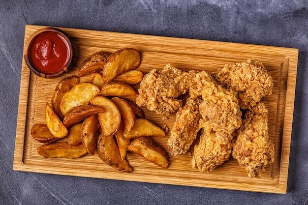 Ali di pollo fritte con fette di patate fritte, vista dall'alto.