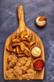 Alette di pollo fritte con fette di patate fritte