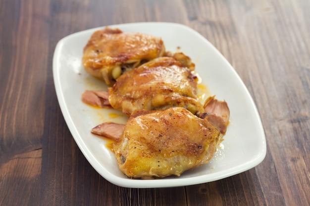Pollo fritto con carne affumicata sul piatto bianco su legno marrone