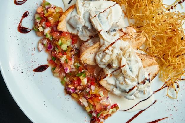 Pollo fritto con salsa di pomodoro e funghi in panna acida e cannucce da patate su un piatto bianco. vista dall'alto