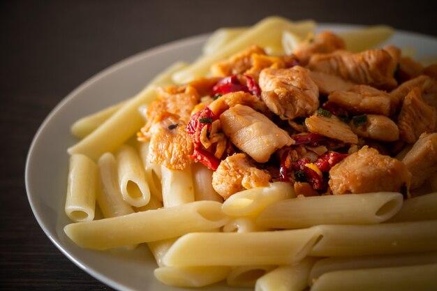 Pollo fritto con pomodori e pasta di penne su un primo piano piatto bianco