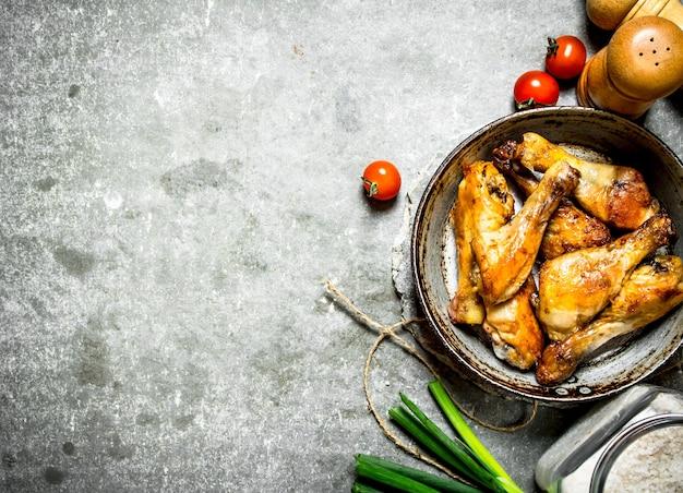 Pollo fritto con verdure e salsa di pomodoro su uno sfondo di pietra
