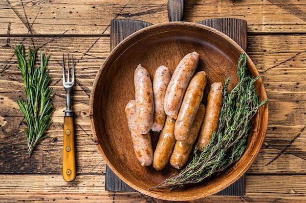 Salsicce fritte di chorizo e bratwurst in un piatto di legno. fondo in legno. vista dall'alto.