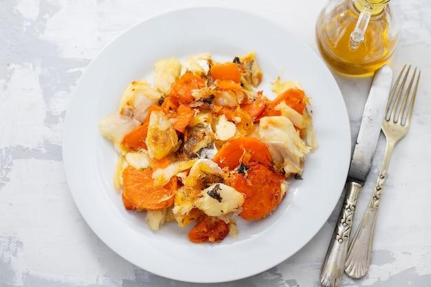 Baccalà fritto con patate dolci sul piatto bianco su fondo in ceramica