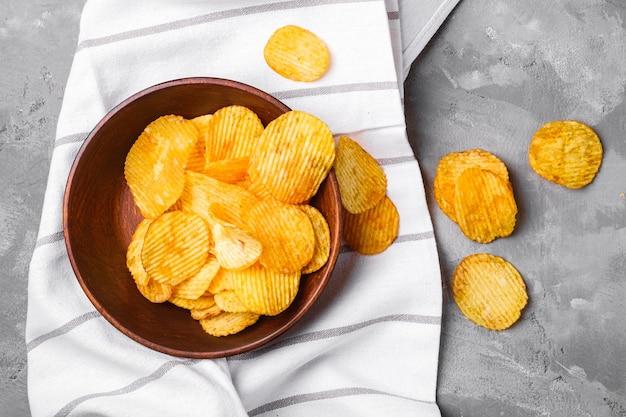 Patatine fritte dorate ondulate fritte in una ciotola di legno marrone sul tovagliolo della tovaglia