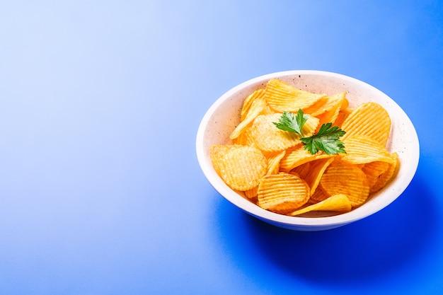 Patatine fritte dorate ondulate fritte con foglia di prezzemolo in una ciotola di legno su sfondo blu