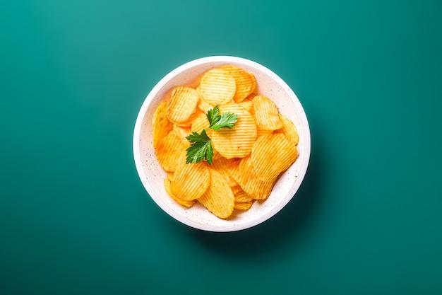 Patatine fritte dorate ondulate fritte con foglia di prezzemolo in una ciotola di legno sul verde Foto Premium