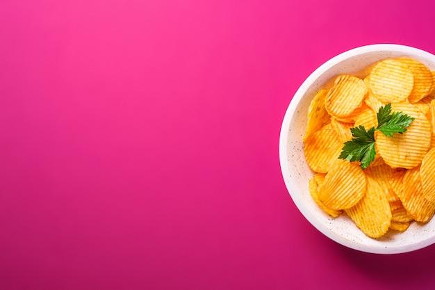 Patatine fritte ondulate dorate con foglia di prezzemolo in una ciotola di legno sul rosa. vista dall'alto