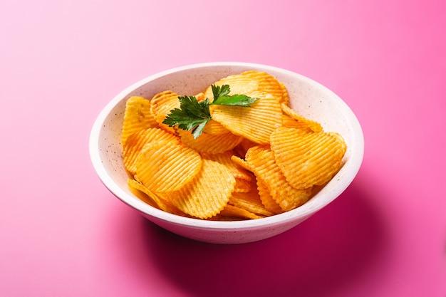 Patatine fritte dorate ondulate fritte con foglia di prezzemolo in una ciotola di legno sul rosa