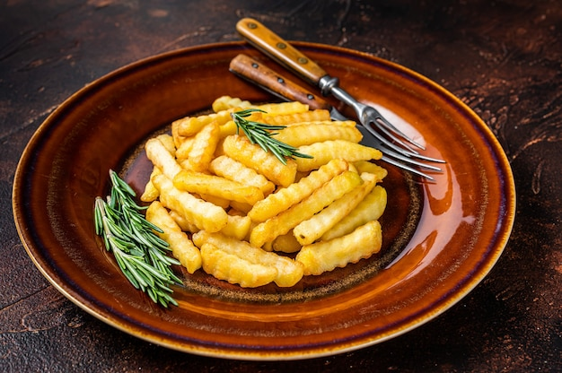 Fried crinkle french fries patate o patatine fritte in un piatto rustico