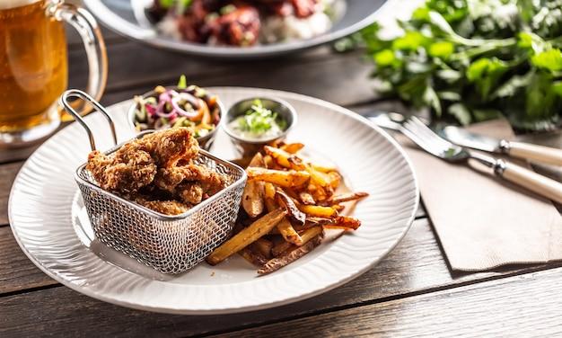 Alette di pollo croccanti fritte con patatine, salsa e insalata servite su un tavolo.
