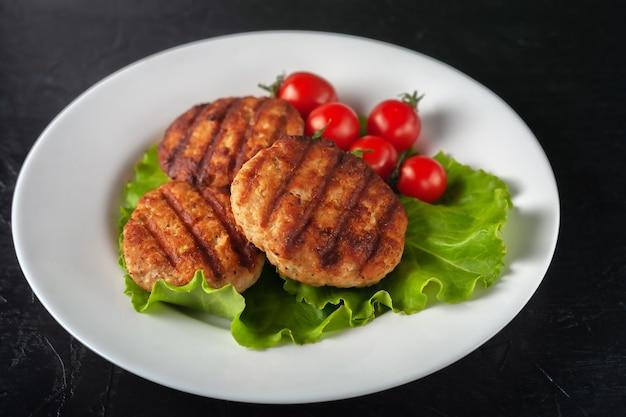 Cotoletta fritta con lattuga e pomodori in un piatto bianco su sfondo nero