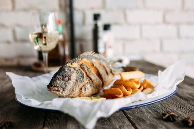 Pesce dorado fritto con patatine fritte e vino bianco