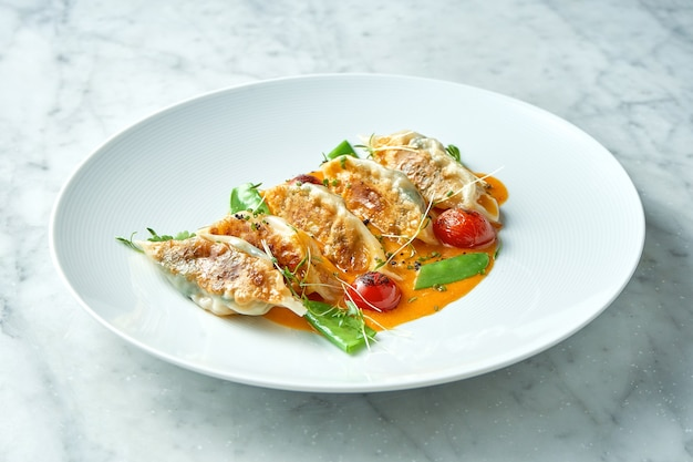 Gnocchi fritti o gyoza giapponese in salsa gialla, pomodorini e piselli, serviti in un piatto bianco su un tavolo di marmo. cucina panasiatica. cibo del ristorante