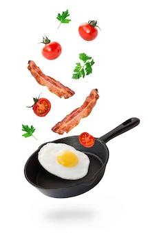 Uovo fritto, pancetta e pomodorini che volano in padella di ferro isolato su bianco.