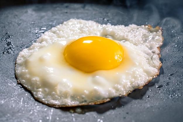 Uovo fritto nella padella nera. messa a fuoco selettiva.