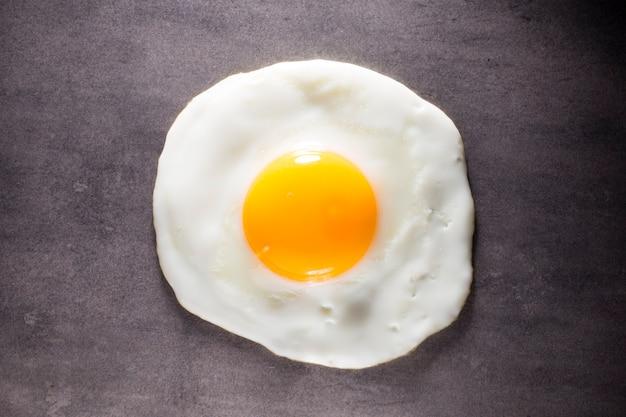 Uovo fritto e sfondo grigio.