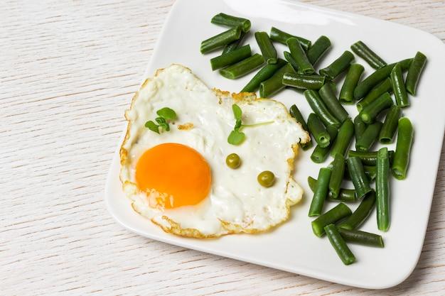 Uovo fritto e fagiolini nel piatto bianco.