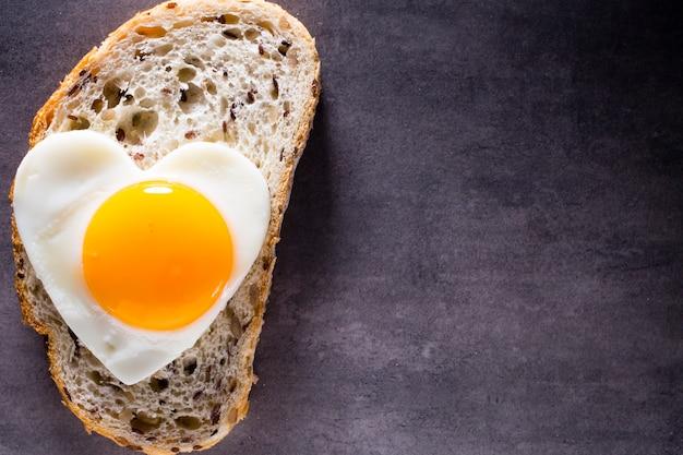 Uovo fritto su fetta di pane a forma di cuore.
