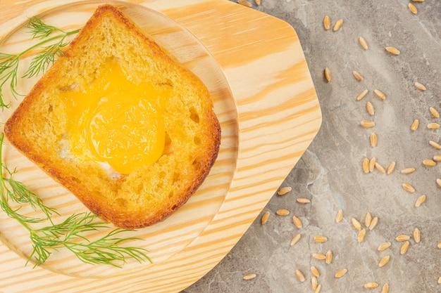 Uovo fritto in toast con aneto fresco su una superficie di pietra