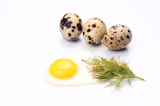 Uovo fritto che si trova accanto alle uova di quaglia su bianco