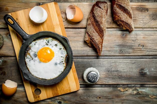 Uovo fritto in padella con pane di segale. su uno sfondo di legno.