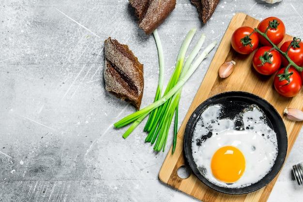 Uovo fritto in padella con pomodori e cipolle verdi. su fondo rustico.