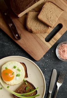 Uovo fritto, fette di pane fritto di segale e sale rosa, vista dall'alto