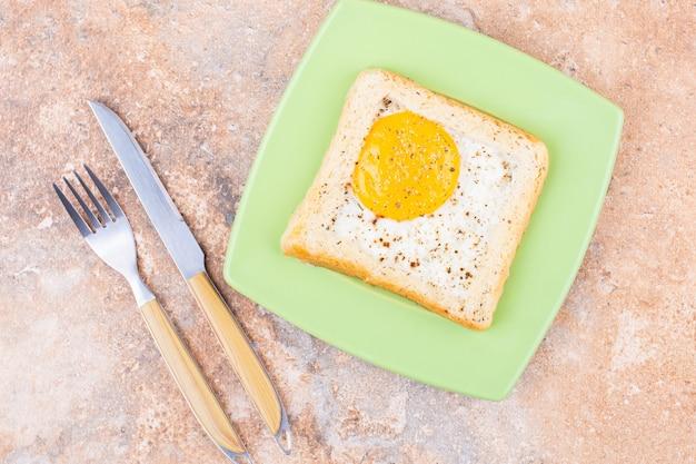 Uovo fritto su un pane a fette su un piatto accanto a coltello e forchetta, sul marmo.