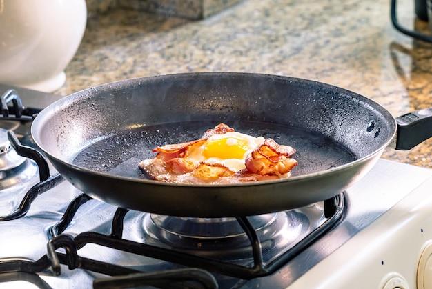 Uovo fritto con pancetta in padella nera. messa a fuoco selettiva.