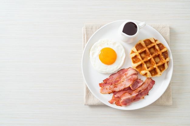 Uovo fritto con bacon e waffle per colazione