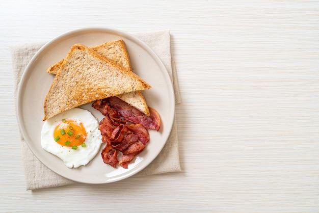 Uovo fritto con pane tostato e pancetta per colazione