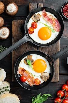 Uovo fritto con ingredienti in padella in ghisa, su vecchio fondo di legno scuro, vista dall'alto piatta