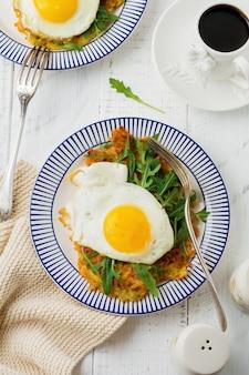 Uovo fritto con frittella di patate, rucola e avocado sul piatto in ceramica per colazione sulla superficie del tavolo in legno bianco