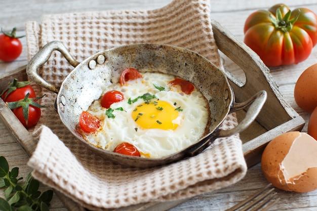 Uovo fritto con pomodori ed erbe aromatiche in una vecchia padella su legno