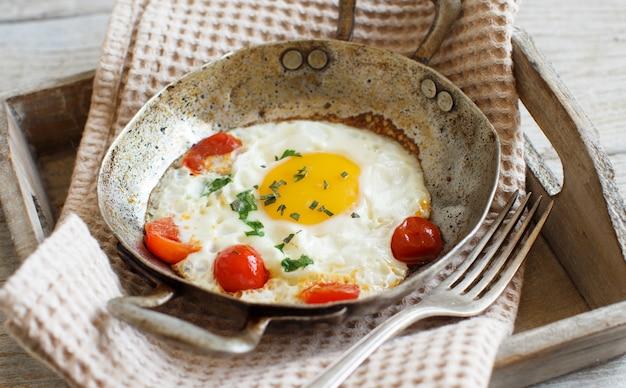 Uovo fritto con pomodori ed erbe su una vecchia padella su legno si chiuda
