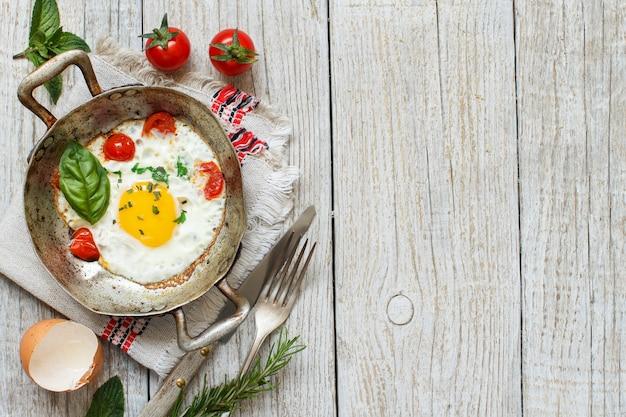 Uovo fritto con pomodori ed erbe su una vecchia padella su legno