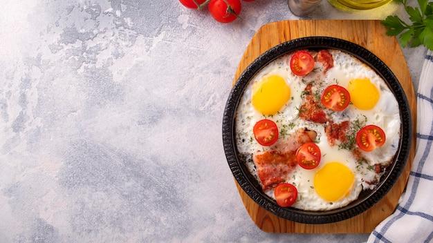 Uova fritte, pancetta e pomodori su una padella antiaderente. concetto di colazione. vista dall'alto. copia spazio