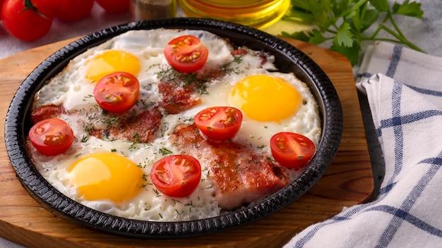 Uova fritte, pancetta e pomodori su una padella antiaderente