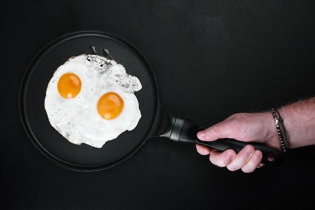 Uova fritte in una padella in mano maschio su sfondo nero, copia dello spazio