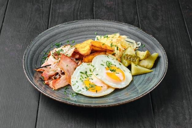 Uova fritte, prosciutto con spicchi di patate, cavolo in salamoia e cetriolo sul tavolo di legno nero