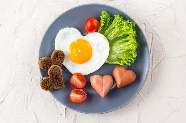 Uova fritte a forma di cuore con salsicce, erbe aromatiche e pomodori. colazione per i vostri cari il giorno di san valentino su sfondo bianco. vista dall'alto con copia spazio