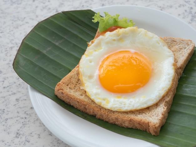 Uova fritte su pane tostato su foglia di banana fresca servite a colazione.