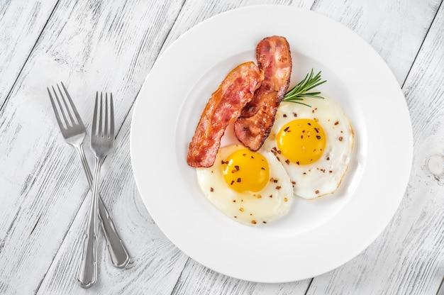 Uova fritte con fette di pancetta sul piatto bianco