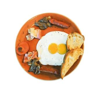 Uova fritte con pancetta salsicce pane arrosto e funghi sul piatto