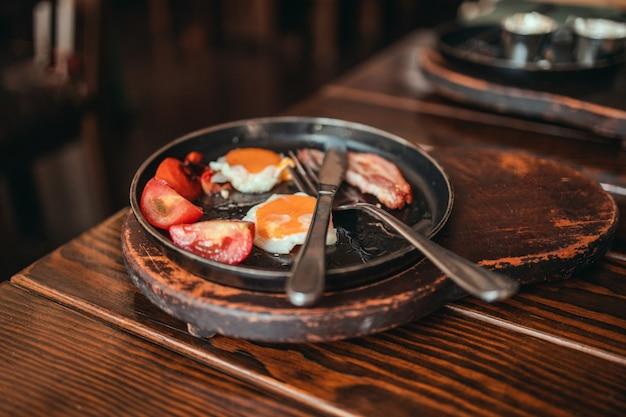 Uova fritte con pancetta, pomodori e toast su un piatto su un tavolo di legno in un caffè