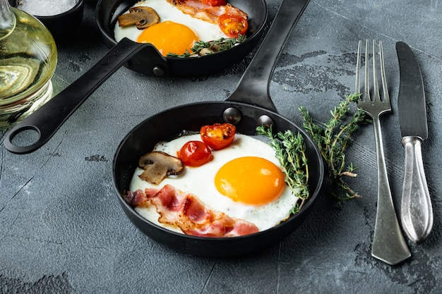 Uova fritte con pancetta e verdure in padella in ghisa, su grigio