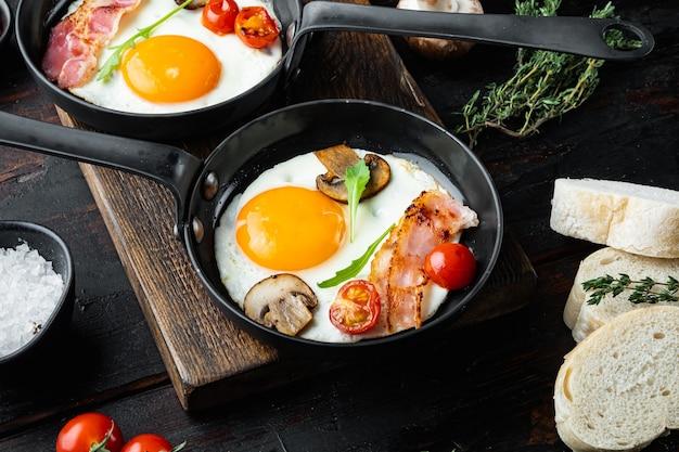Uova fritte con pancetta e verdure in padella in ghisa, sul vecchio tavolo in legno scuro