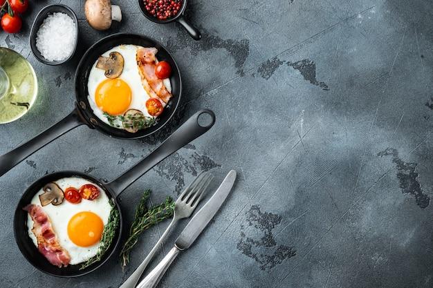 Uova fritte con pomodorini e pane per colazione in padella in ghisa, su sfondo grigio, vista dall'alto piatta, con spazio per copyspace di testo