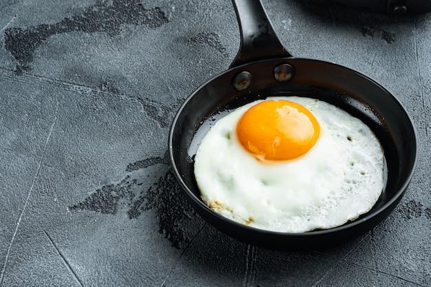 Uova fritte con pomodorini e pane per colazione in padella in ghisa, su grigio